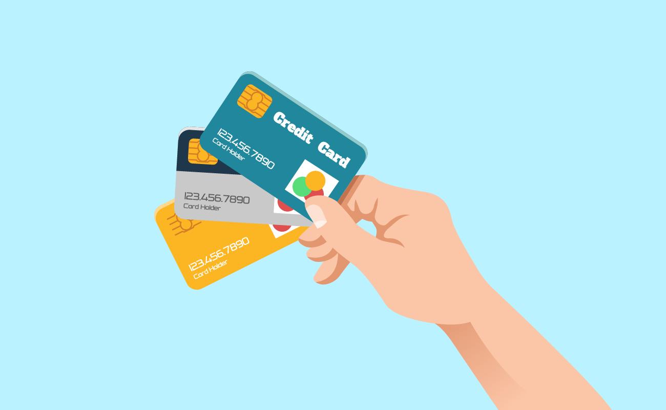 Hand Holding Three Credit Cards.